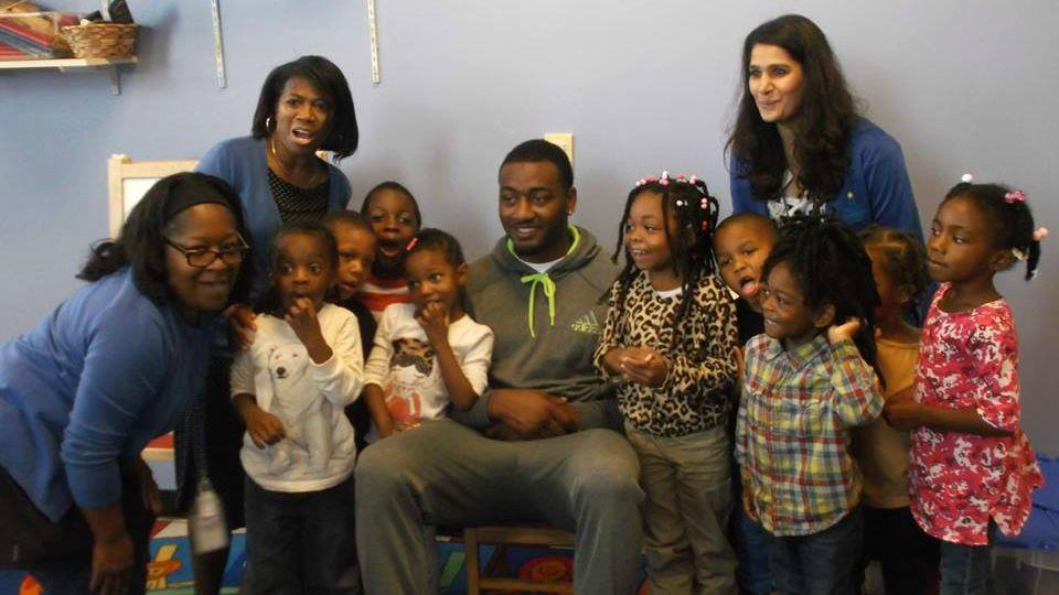 PHOTO COURTESY: BRIGHT BEGINNINGS FACEBOOK PAGE //  JOHN WALL POSES FOR A PICTURE AT BRIGHT BEGINNINGS, A CHARITY THAT PROVIDES EDUCATIONAL SERVICES FOR HOMELESS CHILDREN IN WASHINGTON D.C. (2015)