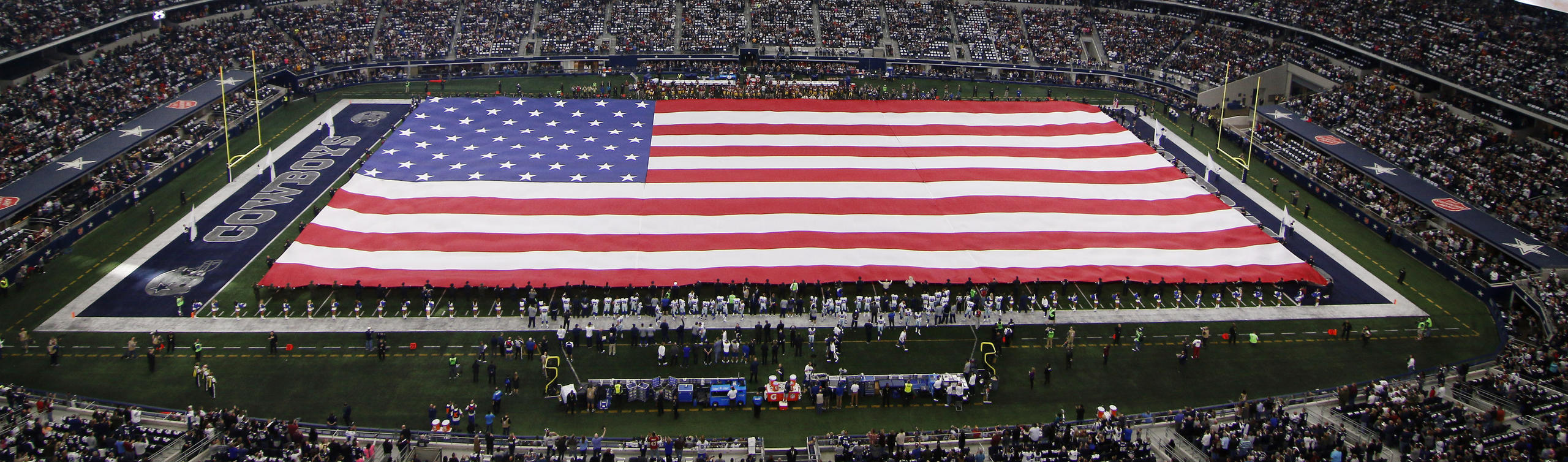 Emergency responders shown on the large video screen unfurl a large American flag inside AT&T stadium during the playing of the national anthem before an NFL football game between the Washington Redskins and Dallas Cowboys on Sunday, Jan. 3, 2016, in Arlington, Texas. The Cowboys were honoring first responders throughout the game. (AP Photo/Roger Steinman)